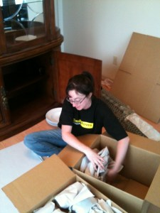 Female packer and mover packing kitchen plates and putting them into a box