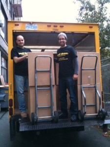 2 men moving office boxes into the truck