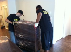2 Movers shrink wrapping a dresser, Yaletown Appartment