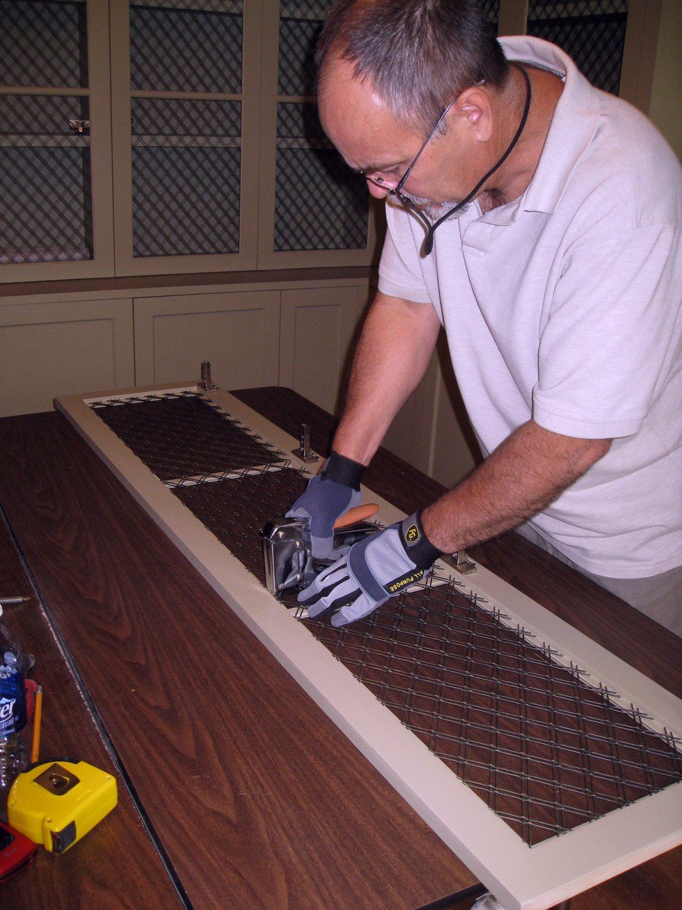 (above) Bert is securing the wire with staples to the inside of the frame on the backside of the cabinet door.