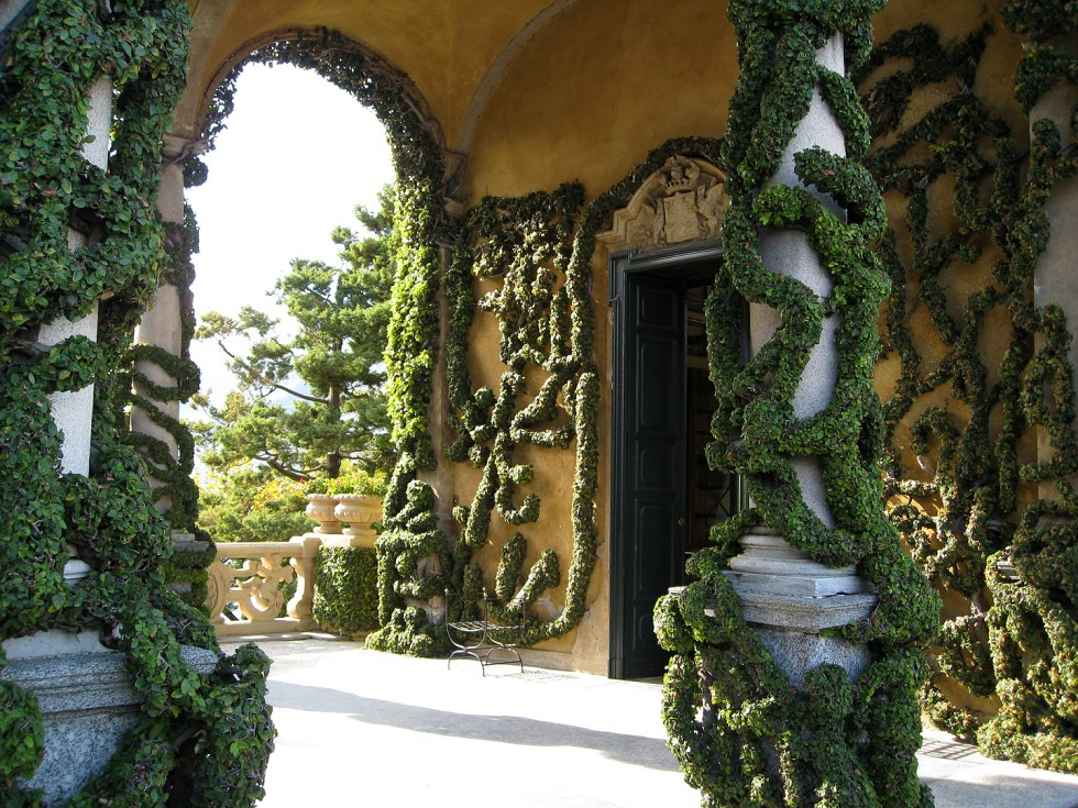 All the massive coils of ivy you see snaking along the walls belong to one single fig ivy plant. This is the veranda of Villa Balbianello. The villa overlooks Lake Como on the tip of a small wooded peninsula on the western shore, and this portion, the loggia, was built by Cardinal Angelo Maria Durini around 1790. It's been said this loggia is where coffee was served for the first time in Italy.
