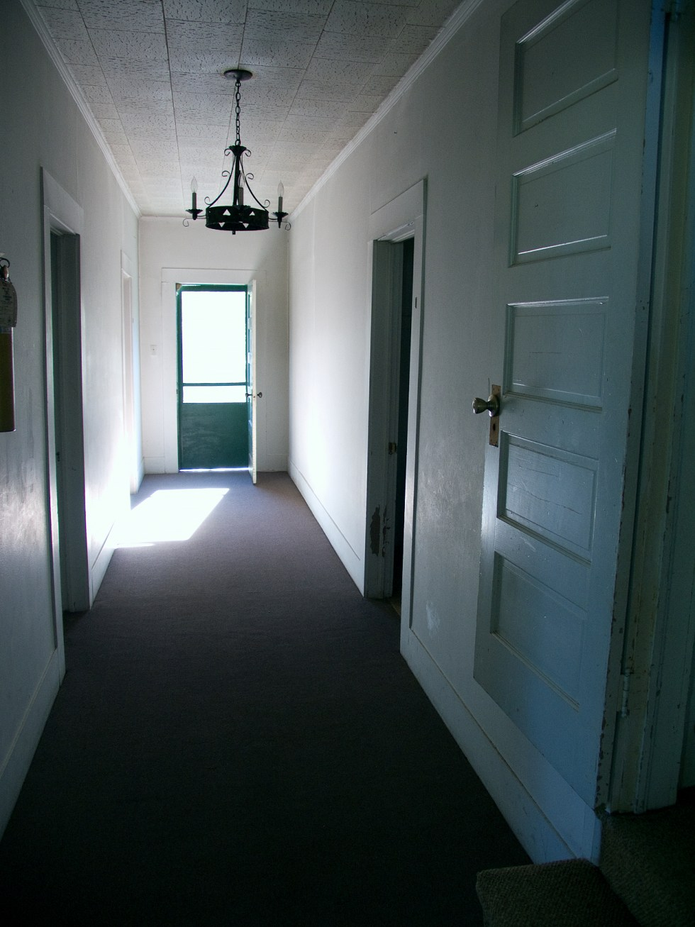 (above) This hallway leads from the living area. To the immediate right, you will see a step leading up to a five panel door which leads to the stair to the second floor. Now why would there be a need to close off the second floor? The ceiling's acoustical tile can't be original.