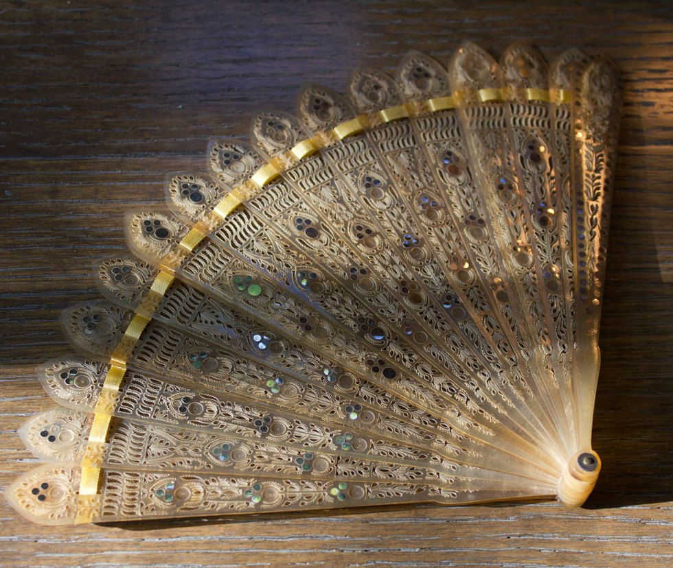 "(above) In the seller's words: ""Antique 19th century brisé fan of blond horn intricately pierced with stylized floral motifs and elaborate tracery accented further by numerous steel sequin piqué inlay to the front."""