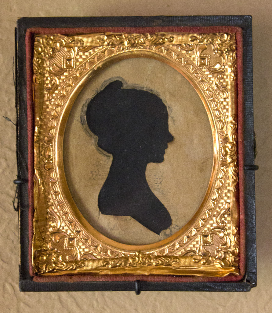 "(above) This is my favorite by far. Tiny, but exquisite. This silhouette is signed ""Wood"" in ink below the bust with ""Mrs. Sally Worster"" penciled below that. Since the sitter looks to be in her early twenties, she, most likely, would have been born during the American Revolution. The frame, a one sixteenth plate ambrotype, is not original to the piece. In fact it is the back portion of a hinged box. The cover portion, now detached, has an American flag with 35 stars. Which means that this frame was created some time between 1863 and 1865 during the height of the Civil War when West Virginia became the thirty fifth state. To be more clear, this silhouette predates the frame by many decades. With Russell's custom captures, this little treasure remains unmarred."
