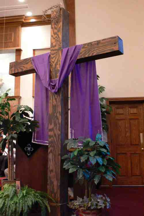 Cross with purple scarf in the front of the church