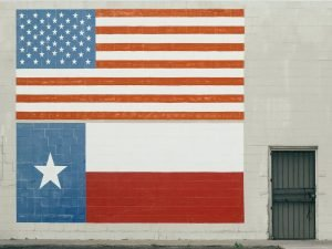 A graffiti of the US and Texan flags side by side, on a white wall.