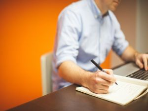 A man doing work at his desk, against an orange background.