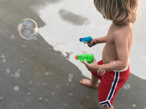 toddler playing with bubbles outside to stay busy