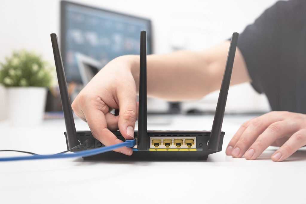 A person plugs an ethernet cable into a router.