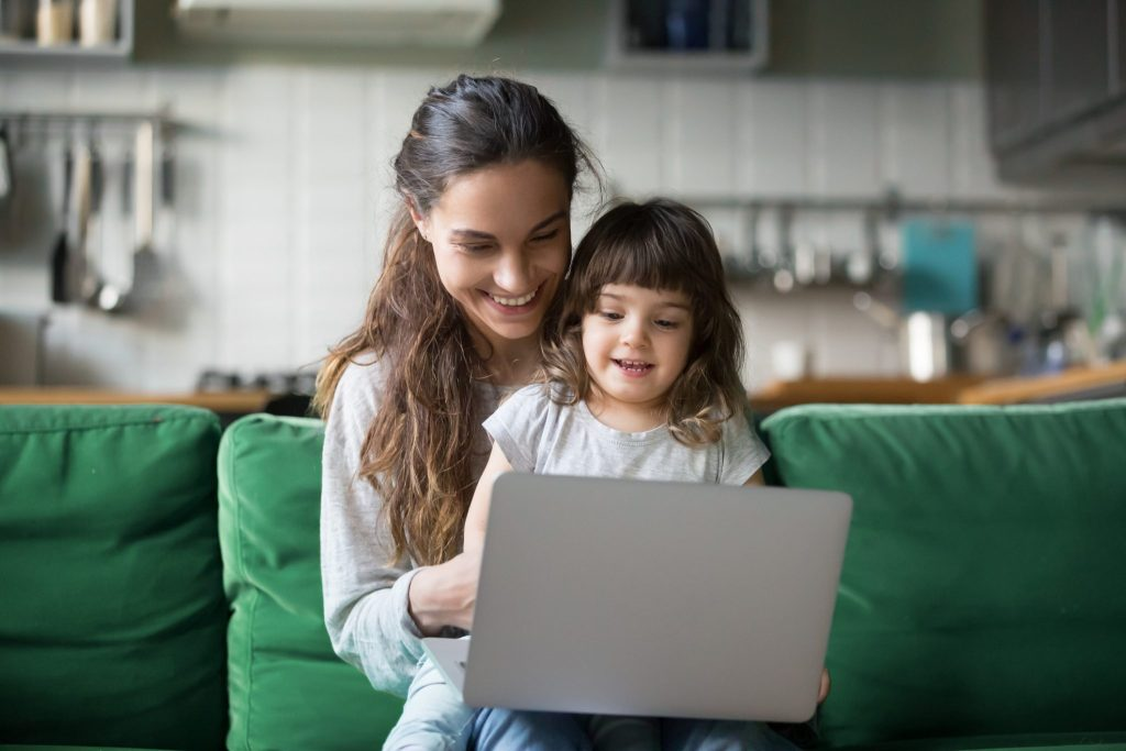 A woman has a tollder on her lap while using a laptop
