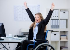 A jubilant business woman at work, sitting in her wheelchair, smiling, and raising her hands and arms into the air