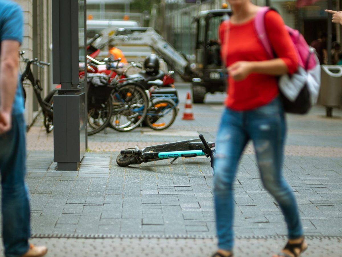 woman walking on pathway beside TIER scooter on road