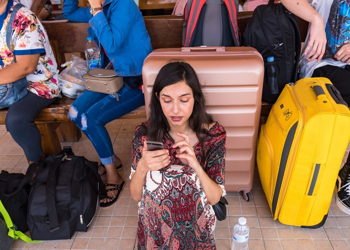 woman studying phone on vacation waiting at train station