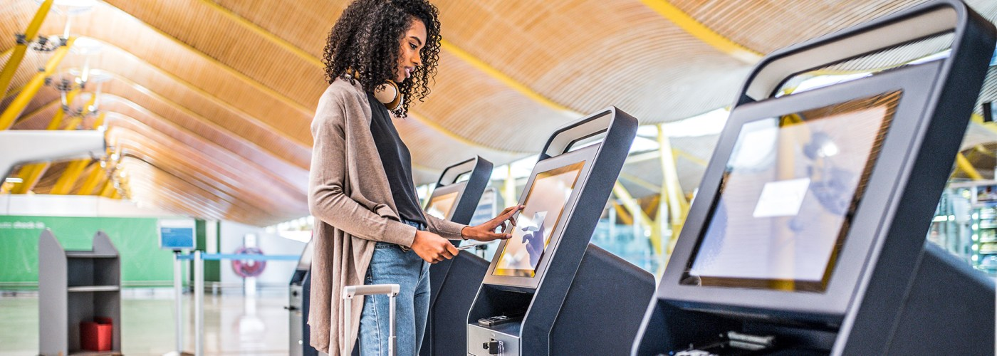 black woman using the check-in machine at the airport getting the boarding pass