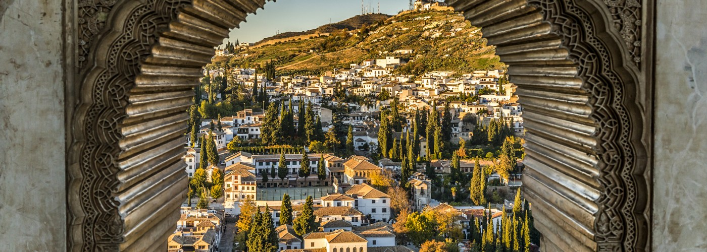 View of the Albayzin district of Granada, Spain, from a window in the Alhambra palace near sunset.