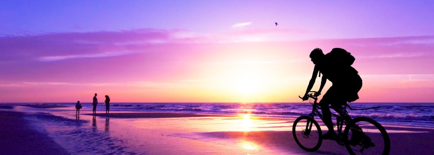 biking on the beach at sunset