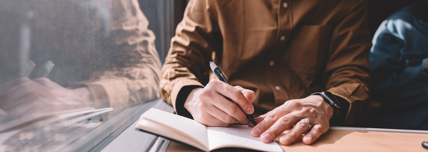man writing in notebook on train