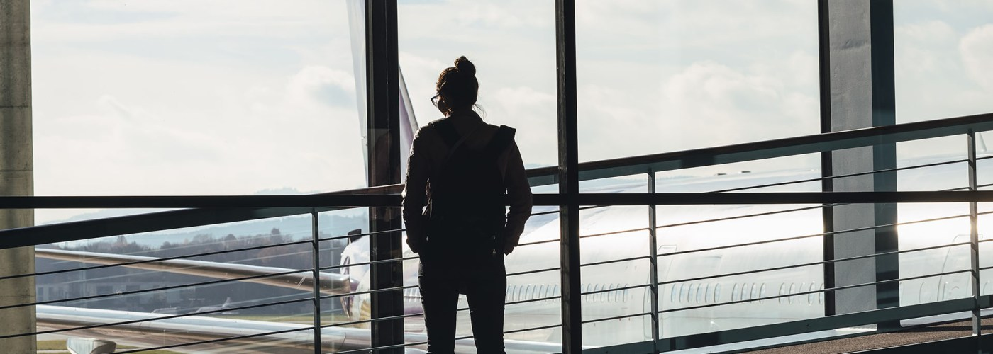 woman looking out airport window.