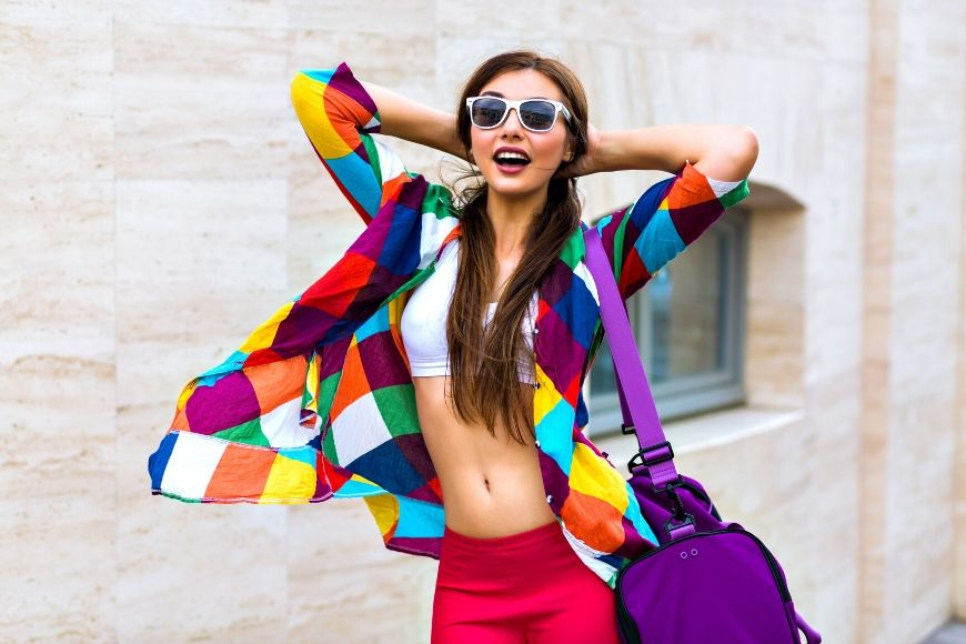 woman in bright colored shirt and purple bag.