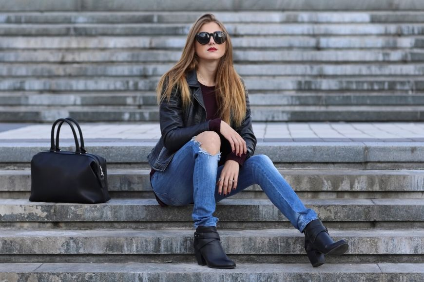 woman in torn skinny jeans on stairs.