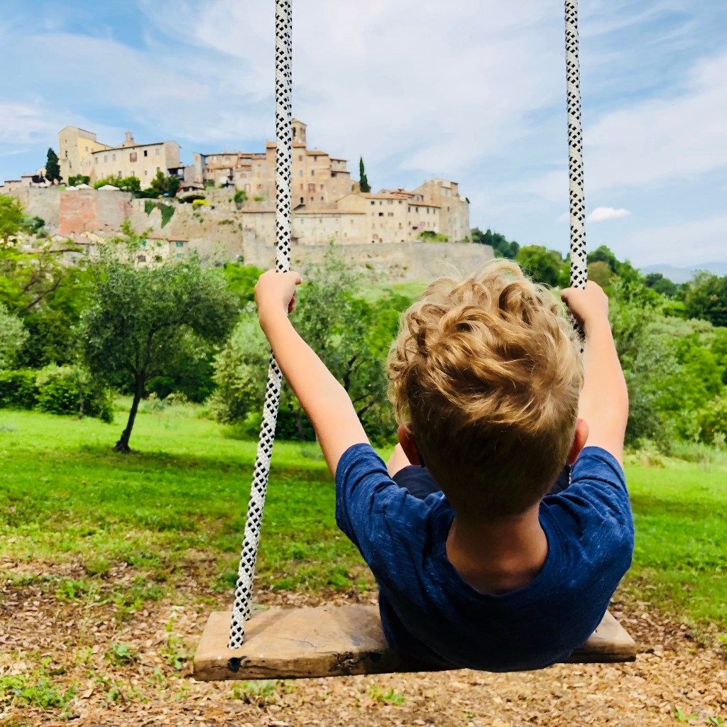 Child swinging with a view of tuscan hill town