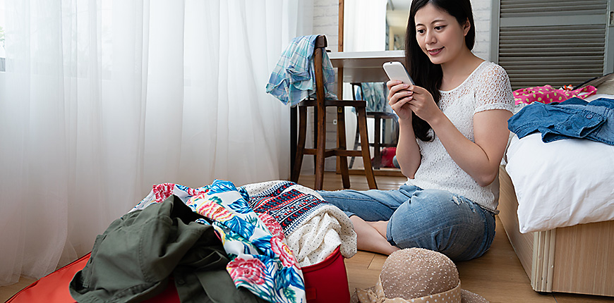young woman looking at her smartphone while packing