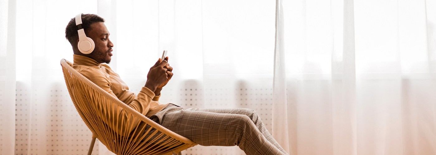Man In Wireless Headset Using Mobile Phone Listening To Audiobook Sitting On Modern Chair Against Window Indoor