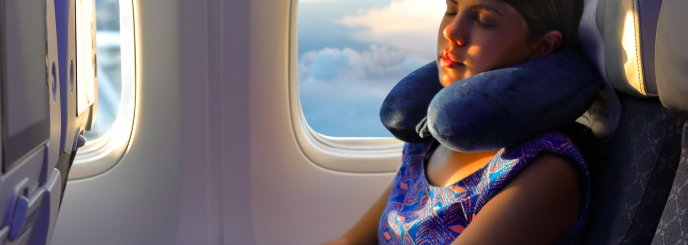 young woman sleeps with a pillow under her head at the window of the airplane during the flight