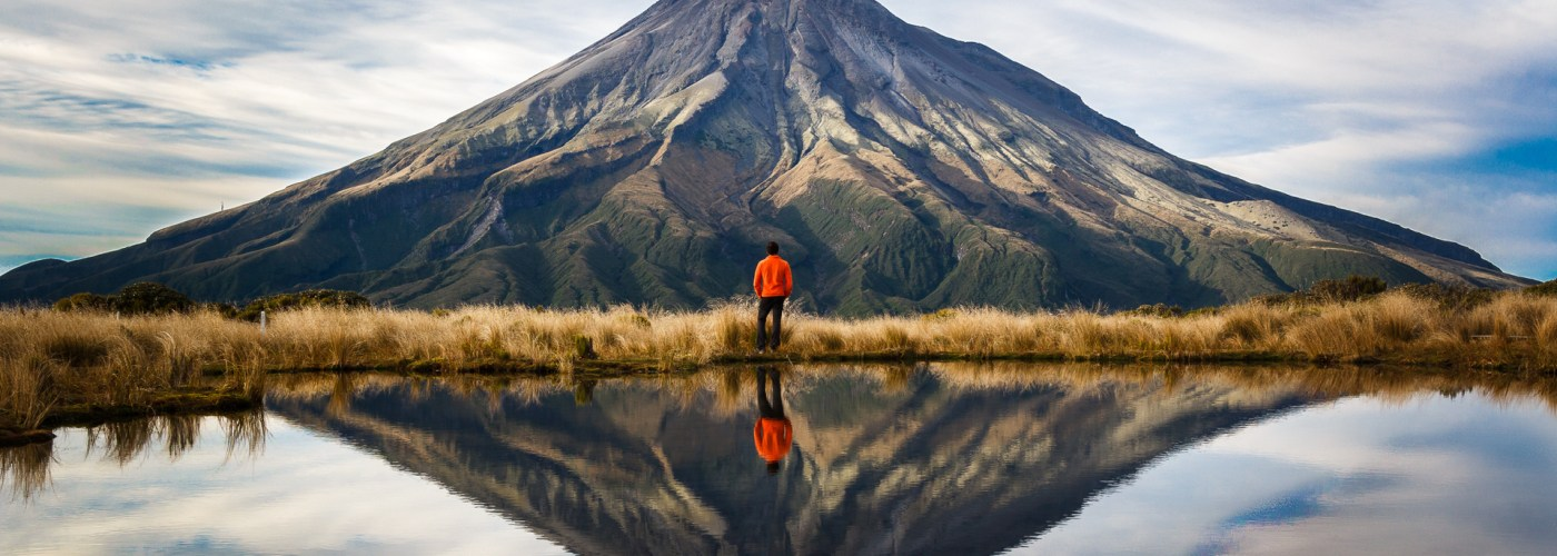 hiker looking at mountain with reflection of water