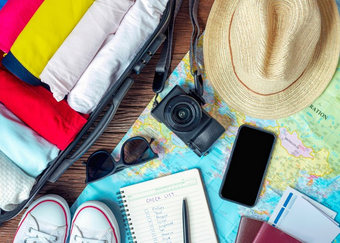 travel items check list camera shoes hat sunglasses and map are displayed on a table