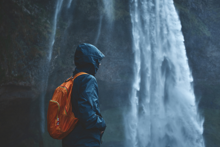 woman in waterproof clothes standing by waterfall.