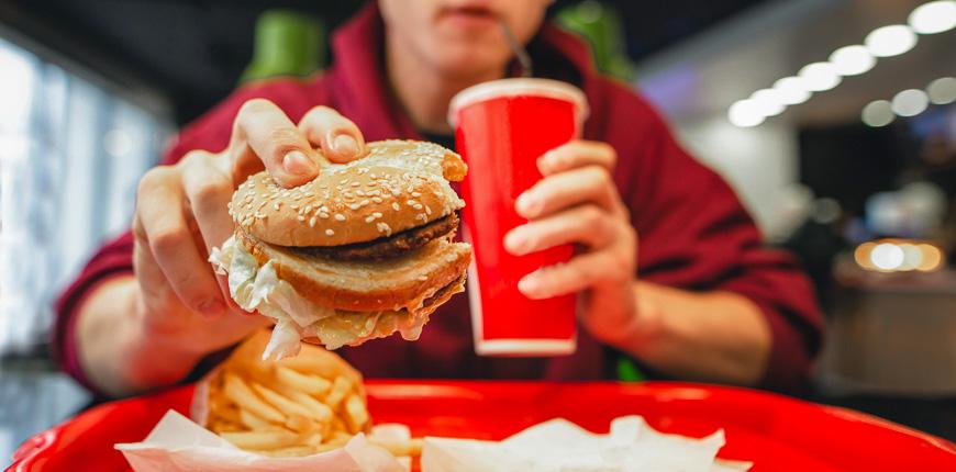 man eating burger sipping soda