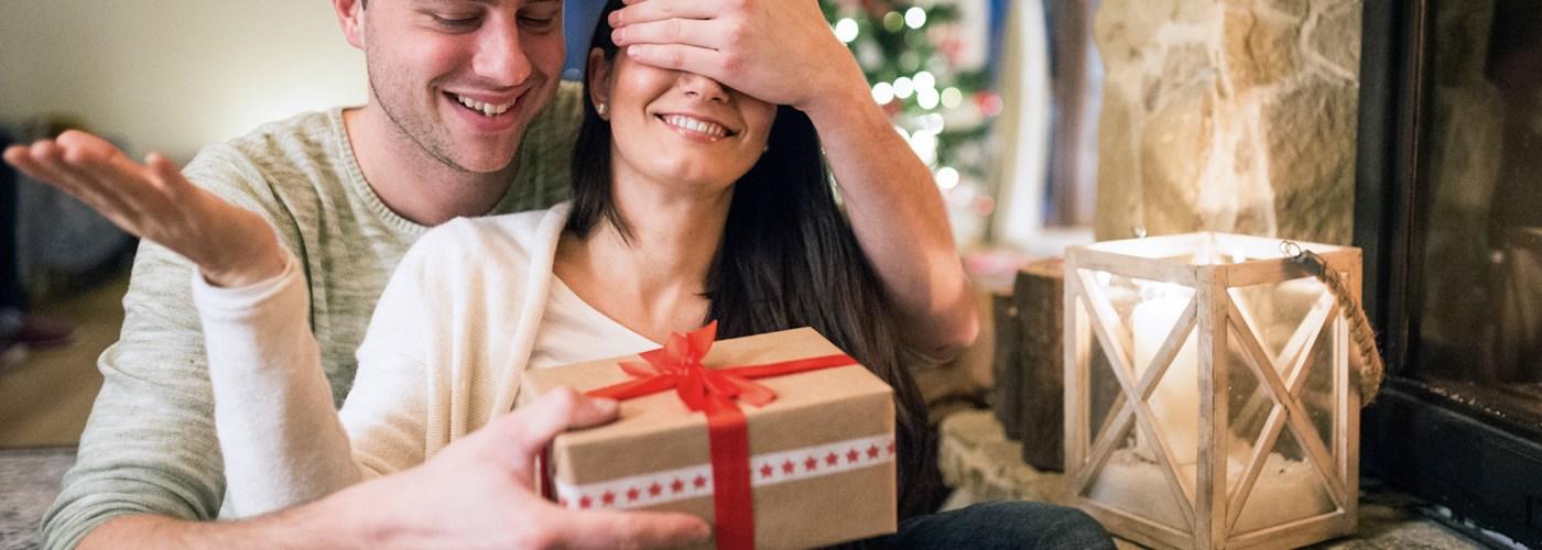 couple opening christmas gift fireplace