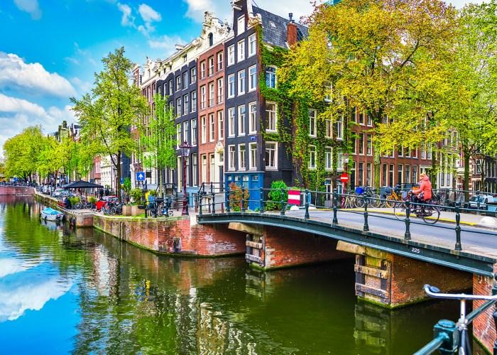 Bridge over channel in Amsterdam Netherlands houses river Amstel landmark old european city spring