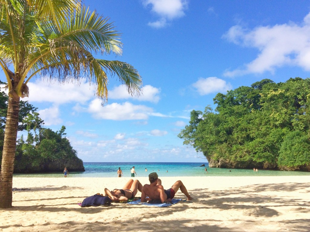 couple lounging on beach in caribbean
