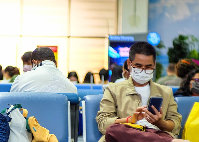 man wearing mask to protect against covid-19 coronavirus sits in airport gate