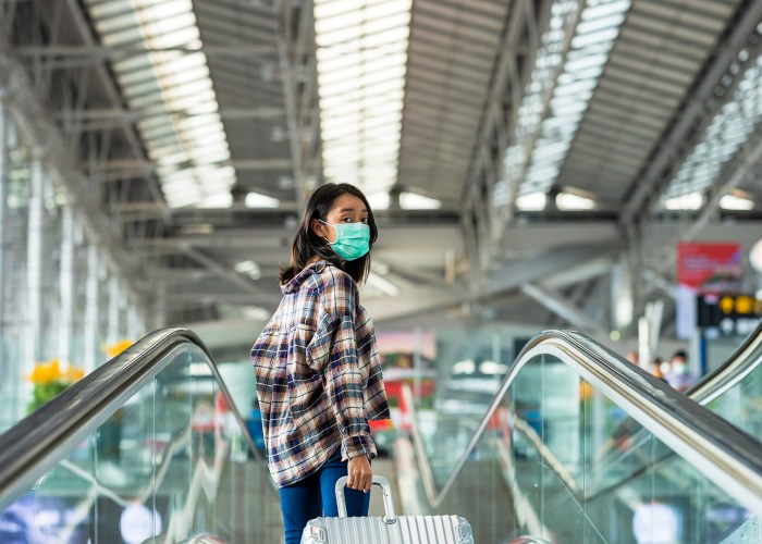 Asian woman tourist wearing face mask protection from coronavirus walking in the airport