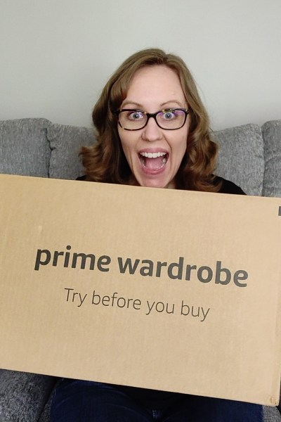 Woman smiling holding a Amazon Prime Wardrobe box