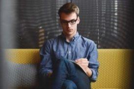 man with eyeglasses reading something