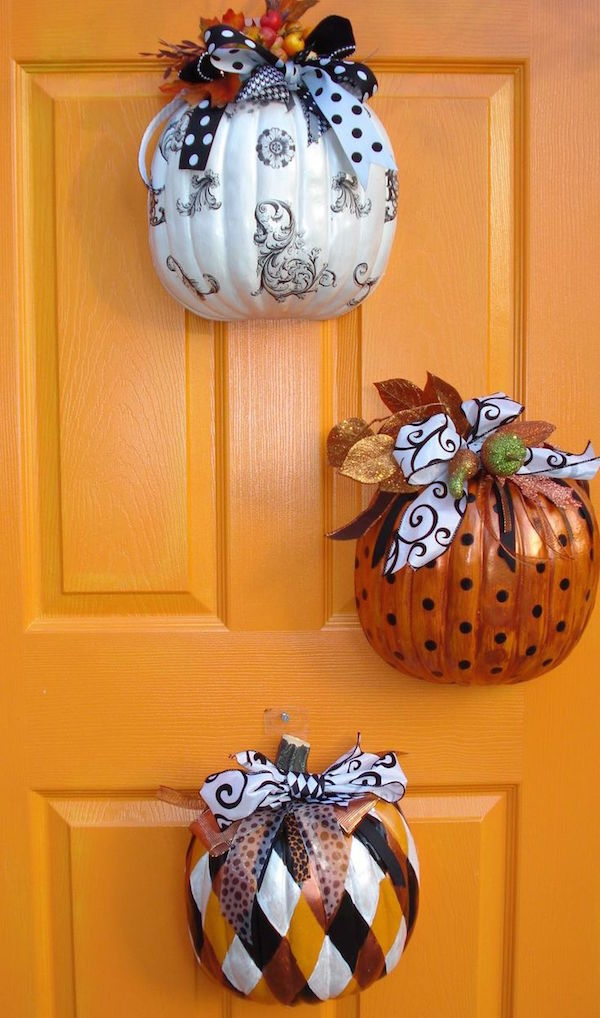 Buy fake pumpkins from the $1 store, cut them in half, decorate the outside, and hang them on your front door! SO smart and pretty!