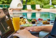 Sitting by pool with laptop