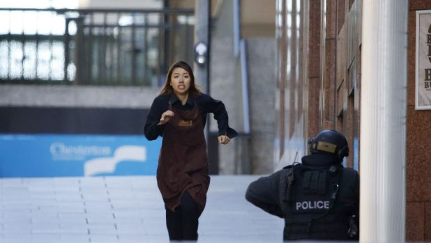 A waitress, believed to be Elly Chen, flees Lindt cafe on Monday afternoon.