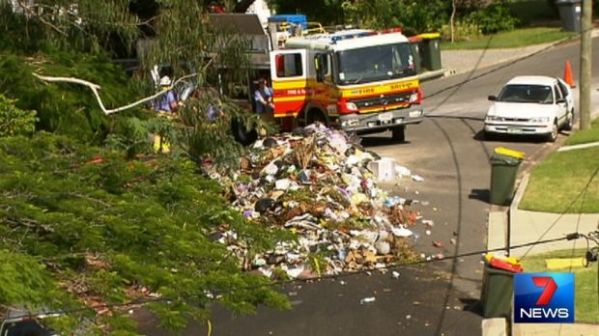 Garbage truck dumps load on street after catching fire