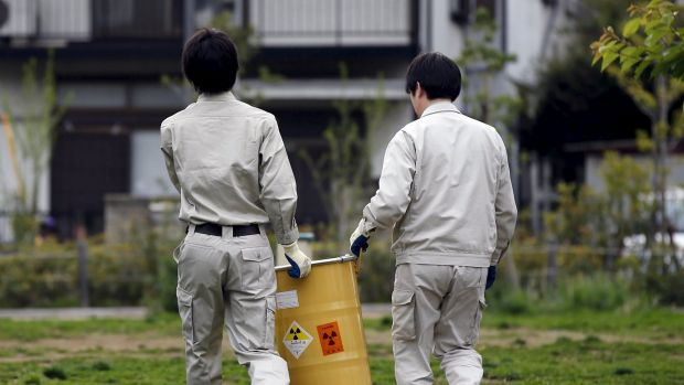 Workers of Tokyo's Toshima ward office carry away a container after it was dug up from the ground near playground equipment at a park in Toshima ward, Tokyo.