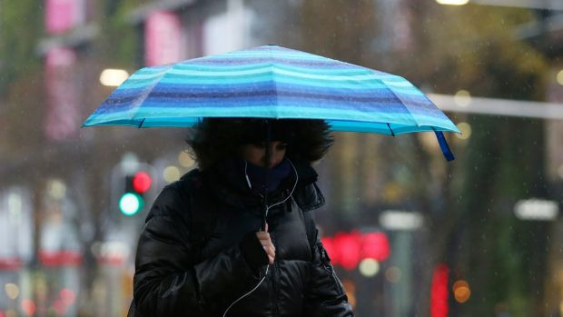 A woman takes cover during rainy weather on Thursday in Sydney.