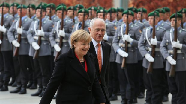 Germany's Chancellor Angela Merkel left, and Prime Minister Malcolm Turnbull review an honour guard during a welcoming ceremony prior to a meeting at the German Chancellery in Berlin.