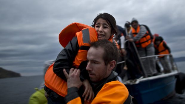 A young girl is carried to shore after making the crossing from the Turkish coast to the Greek island of Lesbos.