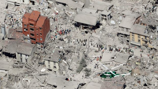 A lone building stands among the grey rubble at Amatrice, as rescuers search for survivors.