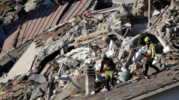 Rescuers make their way through destroyed houses at Pescara Del Tronto.