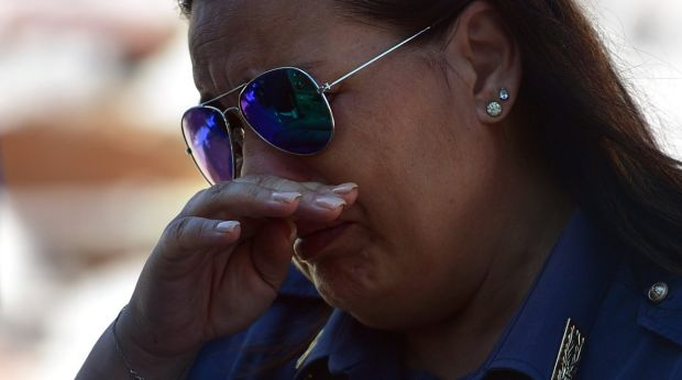 A police officer weeps after viewing damaged buildings in Amatrice.